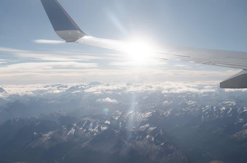Vogelperspektive zu den Bergen und Flugzeug beflügeln mit sunflare stockfotos