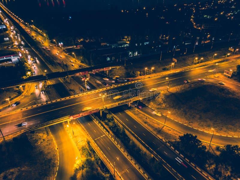 Vogelperspektive zur Straßenkreuzung mit Brücken und Landstraßen, zur modernen Stadt mit Nachtbeleuchtung und zum Autoverkehr stockfotografie