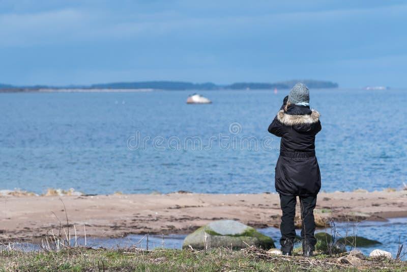 Vogelweibchenbeobachter durch die Küste lizenzfreies stockfoto