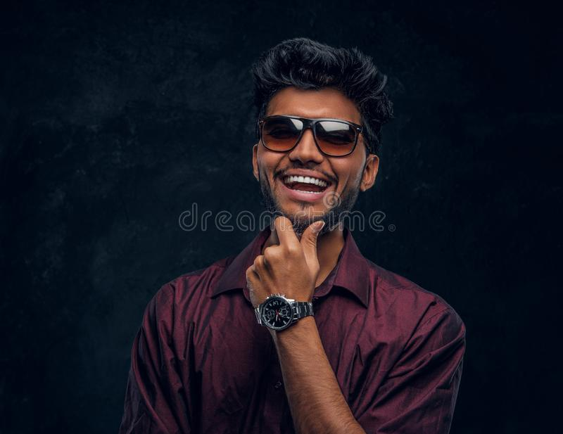 Vogue, fashion, style. Cheerful young Indian guy wearing a stylish shirt and sunglasses posing with hand on chin. Studio photo against a dark textured wall stock photography