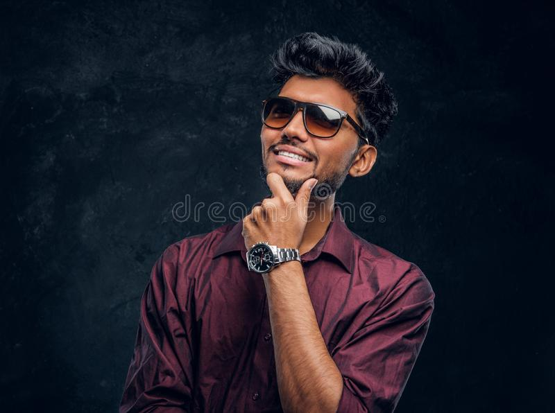 Vogue, fashion, style. Cheerful young Indian guy wearing a stylish shirt and sunglasses posing with hand on chin. Studio photo against a dark textured wall stock images