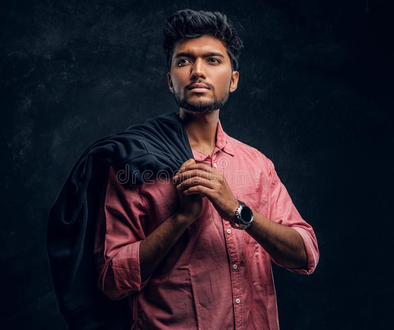 Vogue, fashion, style. Handsome young Indian guy wearing a pink shirt holding a jacket on his shoulder and looking. Sideways. Studio photo against a dark stock photography