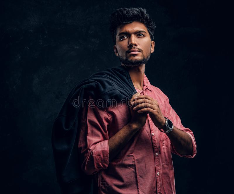 Vogue, fashion, style. Handsome young Indian guy wearing a pink shirt holding a jacket on his shoulder and looking. Sideways. Studio photo against a dark stock photos