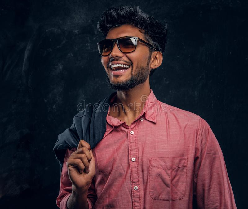 Vogue, fashion, style. Handsome young Indian guy wearing a pink shirt and sunglasses holding a jacket on his shoulder. Smiling and looking sideways. Studio royalty free stock photo