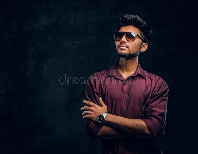 Vogue, fashion, style. Handsome young Indian guy wearing a stylish shirt and sunglasses posing with crossed arms. royalty free stock photo