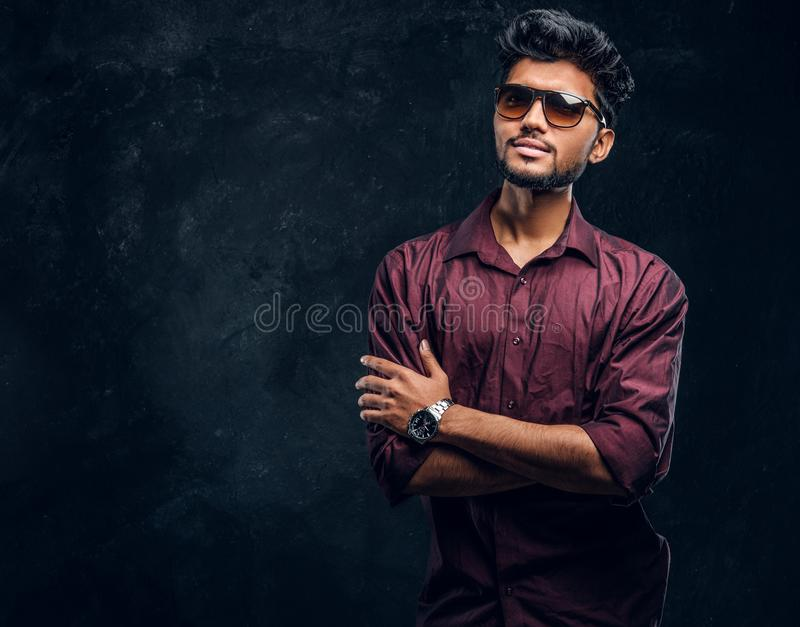 Vogue, fashion, style. Handsome young Indian guy wearing a stylish shirt and sunglasses posing with crossed arms. stock photos