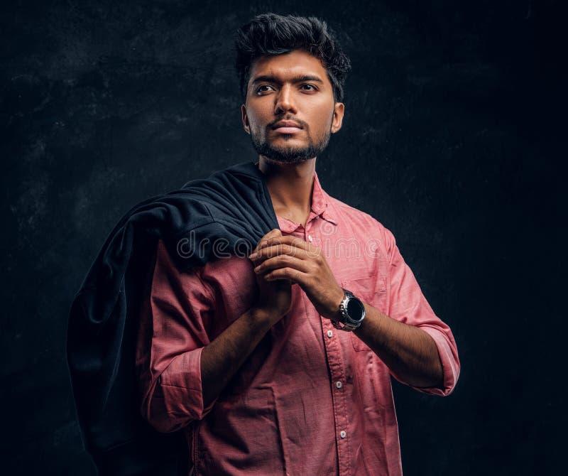Vogue, manier, stijl Knappe jonge Indische kerel die een roze overhemd dragen die een jasje bij zijn schouder en het kijken houde stock fotografie