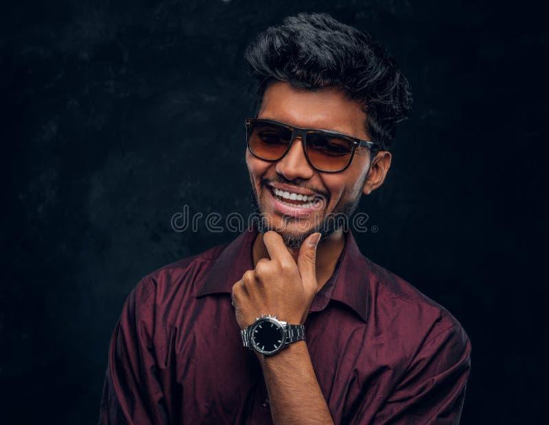 Vogue, manier, stijl Vrolijke jonge Indische kerel die een modieus overhemd en zonnebril dragen die met hand op kin stellen stock afbeelding