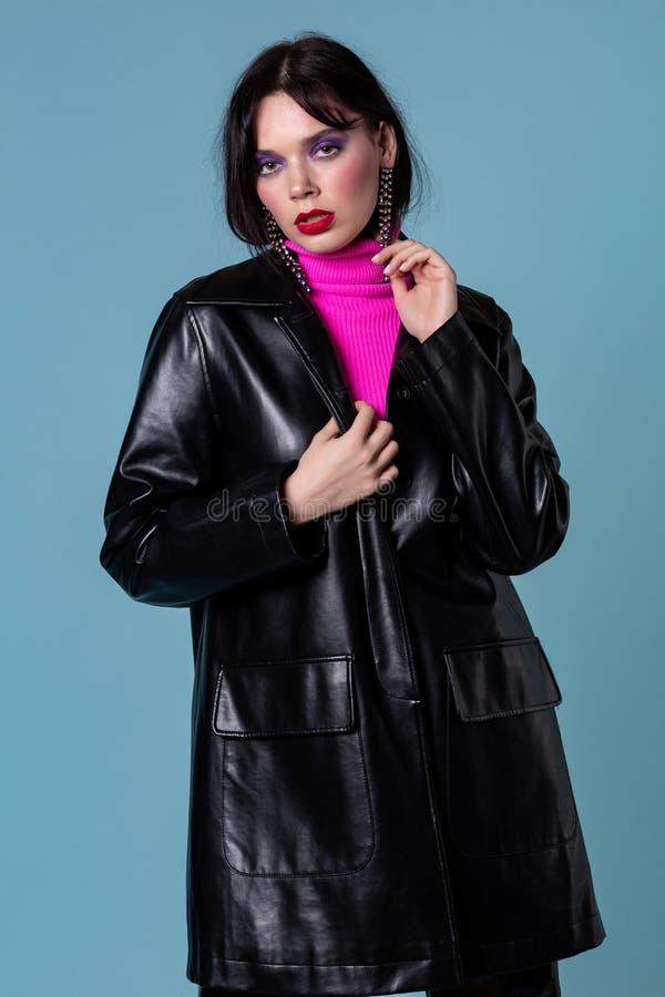 Vogue modell i läderomslag med mörkt hår och färgrik makeup royaltyfria foton