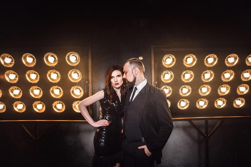 Vogue and sensual concept. Elegant celeb couple posing on the stage near lamp royalty free stock photos