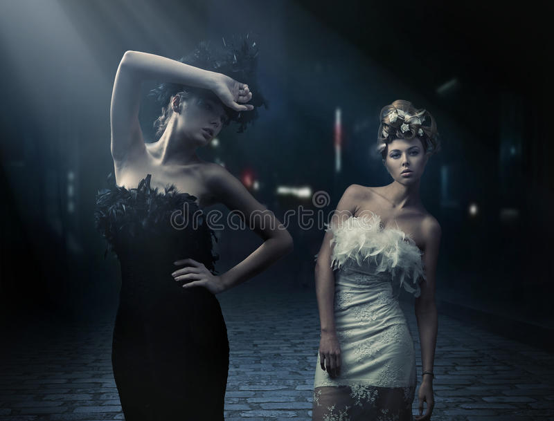 Vogue style photo of a two fashion ladies. Over city background royalty free stock photography