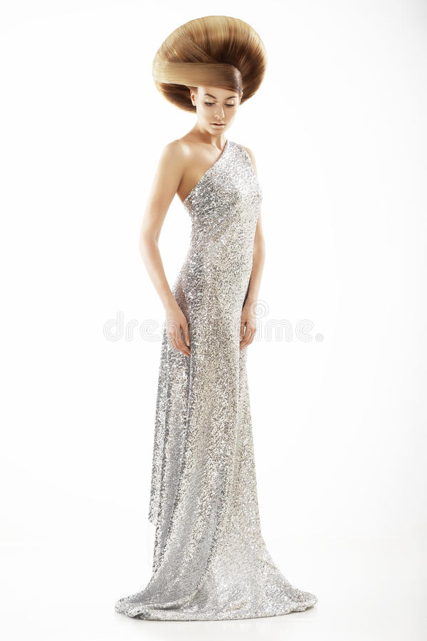 Vogue Style. Trendy Woman in Silver Silky Dress and Creative Hairstyle. Trendy Woman in Silver Silky Dress and Creative Hairstyle stock photo