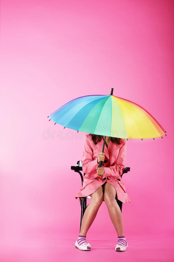 Vogue. Woman in Pink Coat sitting with Colorful Umbrella. Fashion Style. Person in Pink Coat sits with big Umbrella stock photo