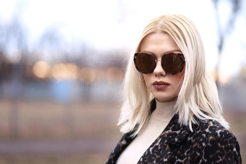 Voguish woman. Voguish young blond woman in leopard coat with sunglasses walking on the street in sunset royalty free stock photos