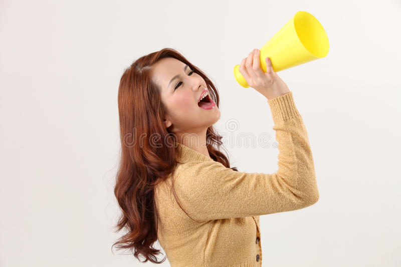 Voice out. Woman screaming into the bullhorn royalty free stock photo