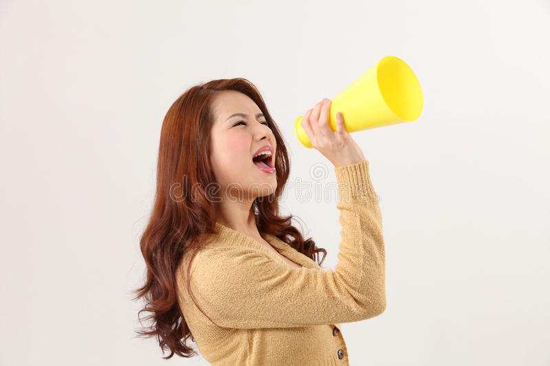 Voice out. Woman screaming into the bullhorn stock photography