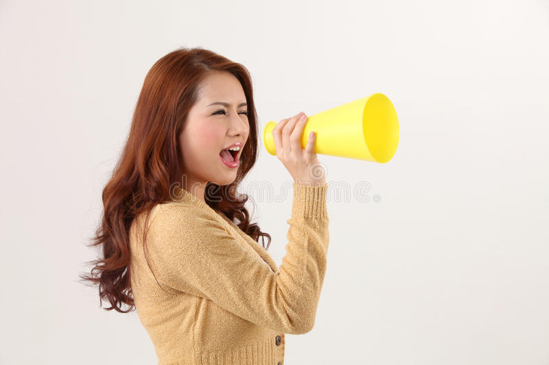 Voice out. Woman screaming into the bullhorn royalty free stock photos