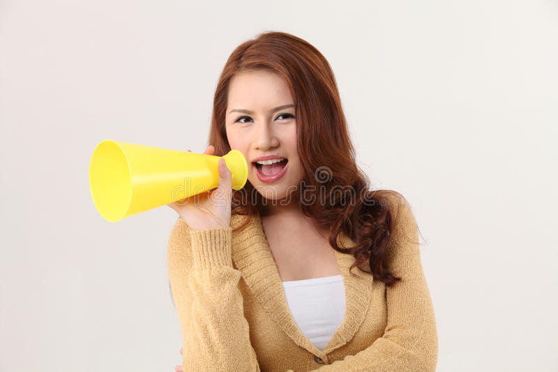Voice out. Woman screaming into the bullhorn stock photos