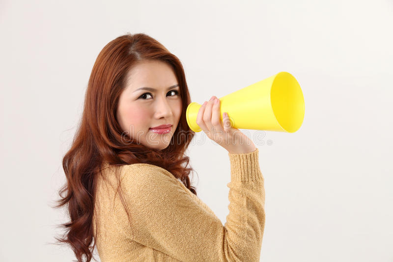 Voice out. Woman screaming into the bullhorn stock photo