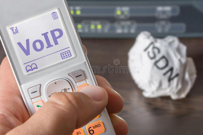 Voice over IP as the new standard of telecommunication in the office. Man holds a telephone receiver in his hand, on the display of which VoIP can be read and in stock photos