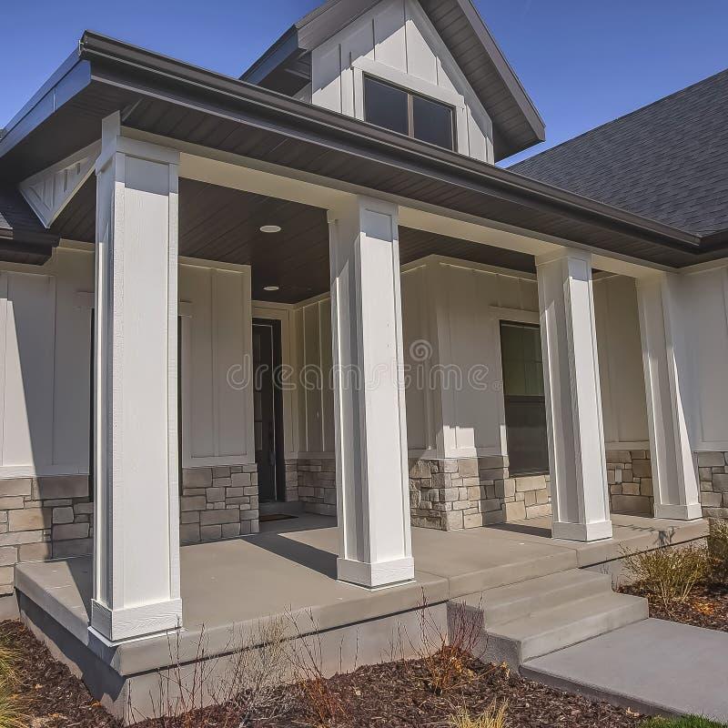 Voie carrée et escaliers menant au porche avec des piliers à la façade d'une maison photos stock