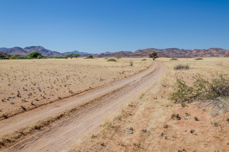 Voie de désert de Sandy menant par le paysage aride vers les collines rocheuses, désert de Namib, Angola photos libres de droits