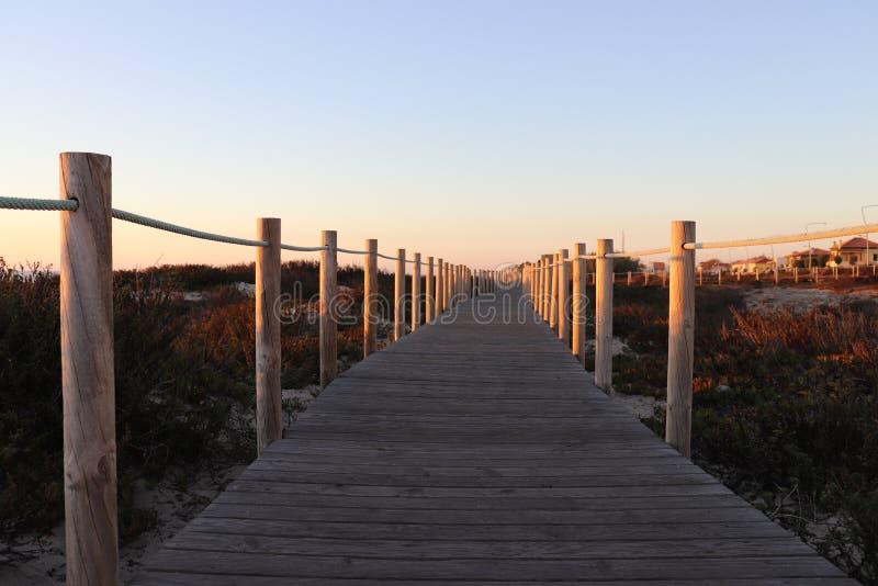 Voie en bois par la mer pendant le coucher du soleil photographie stock