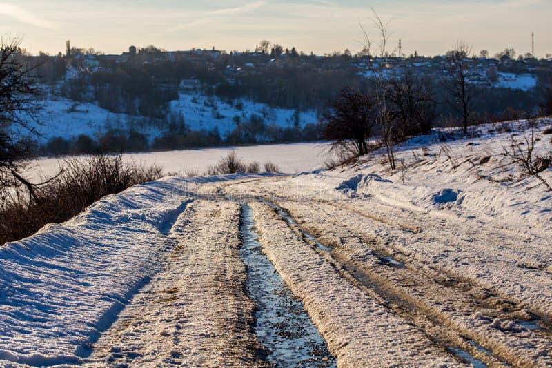 Voie rustique de route à la lumière du jour de dégel d'hiver avec personne et le foyer sélectif photographie stock libre de droits