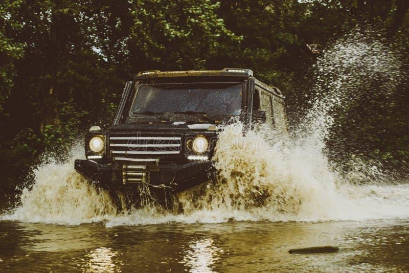 Voie sur la boue voiture tous terrains du suv 4x4 Voies sur un champ boueux La jeep s'est ?cras?e dans un magma et a pris un pulv image libre de droits