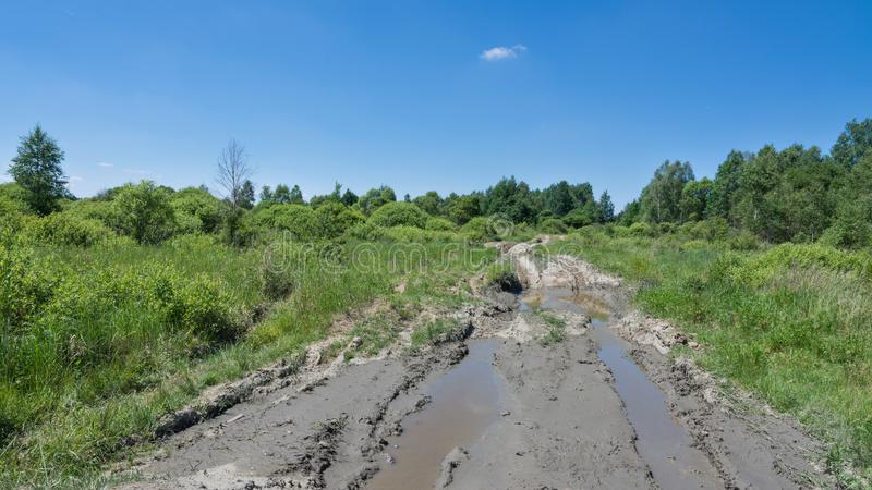 Voie tous terrains avec des magmas et des empreintes de pneu en paysage d'été et ciel bleu photographie stock libre de droits