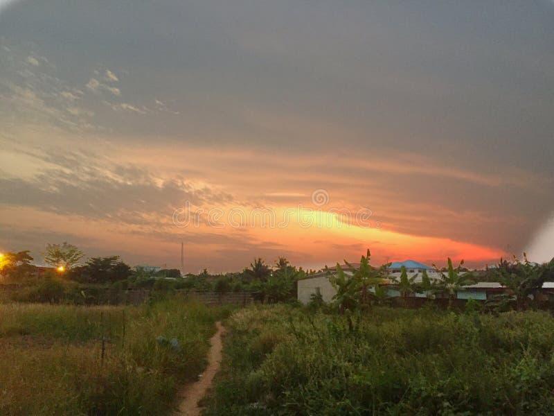 Voies dans un buisson avec un coucher du soleil coloré au Ghana images stock