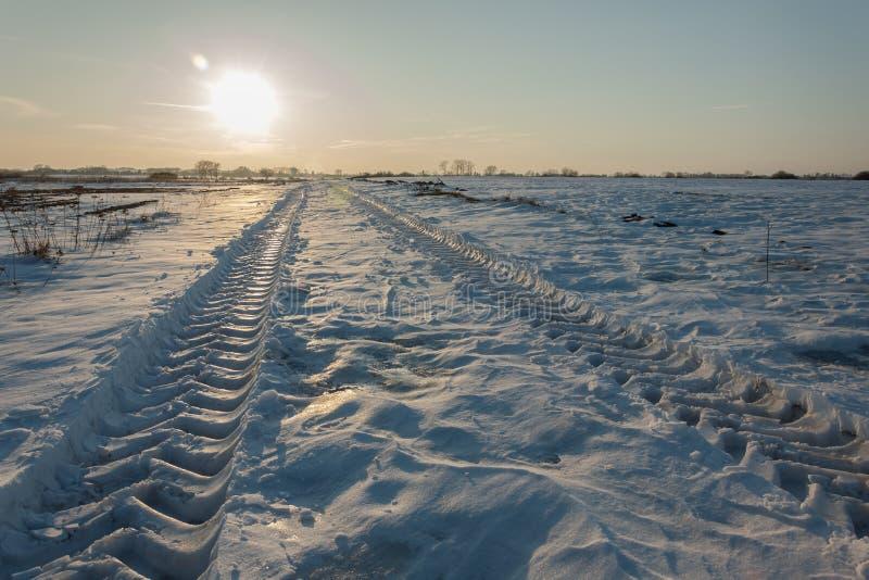 Voies de pneu de véhicule sur la neige et le soleil au-dessus de l'horizon photographie stock libre de droits