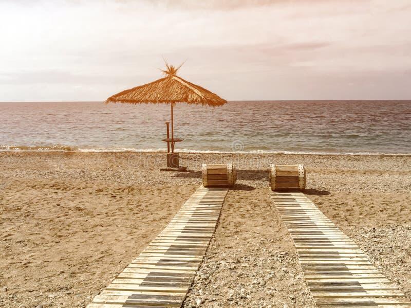 Voies de Reed vers la mer sur une plage sablonneuse et un parapluie de paille un jour d'été dans les tropiques image libre de droits