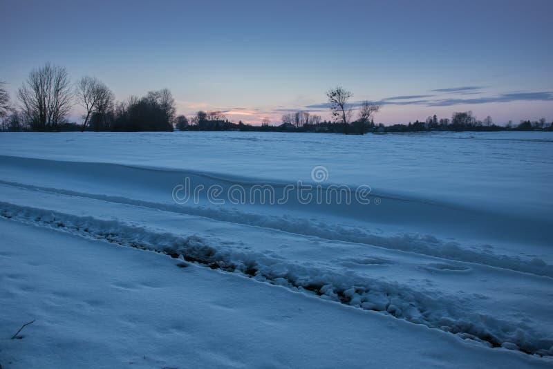 Voies de roue sur la neige et congères sur le champ images stock