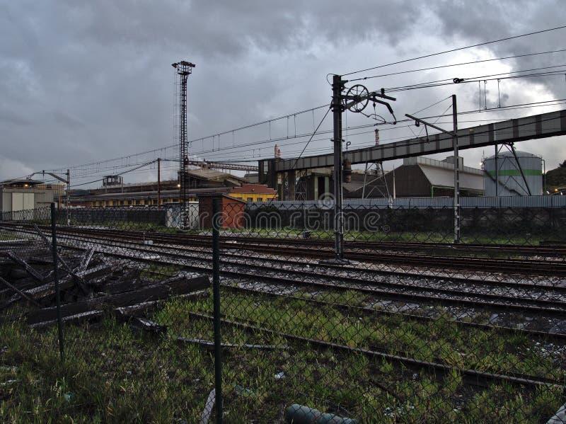 Voies de train en mauvais état près d'une zone industrielle obsolète image stock