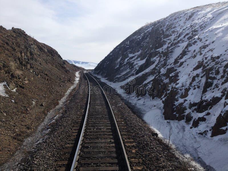 Voies de train sur les montagnes neigeuses images stock