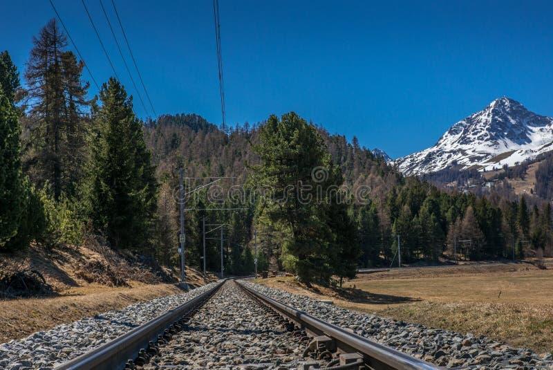 Voies des chemins de fer de Raetian menant aux montagnes - 2 images stock