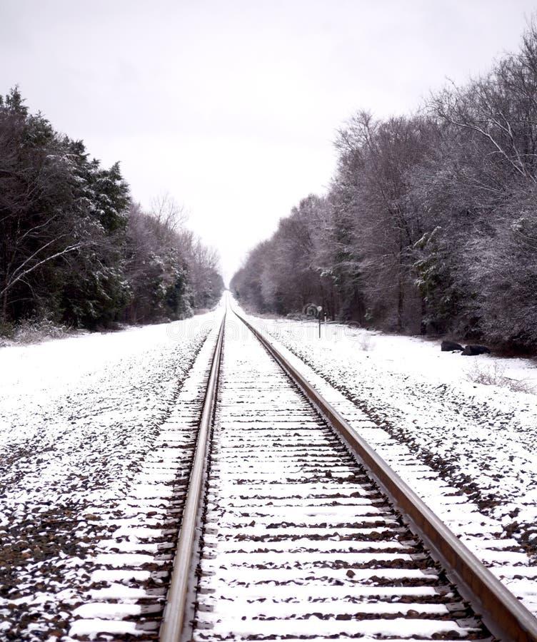 Voies ferrées dans la neige menant dans l'infini photo stock