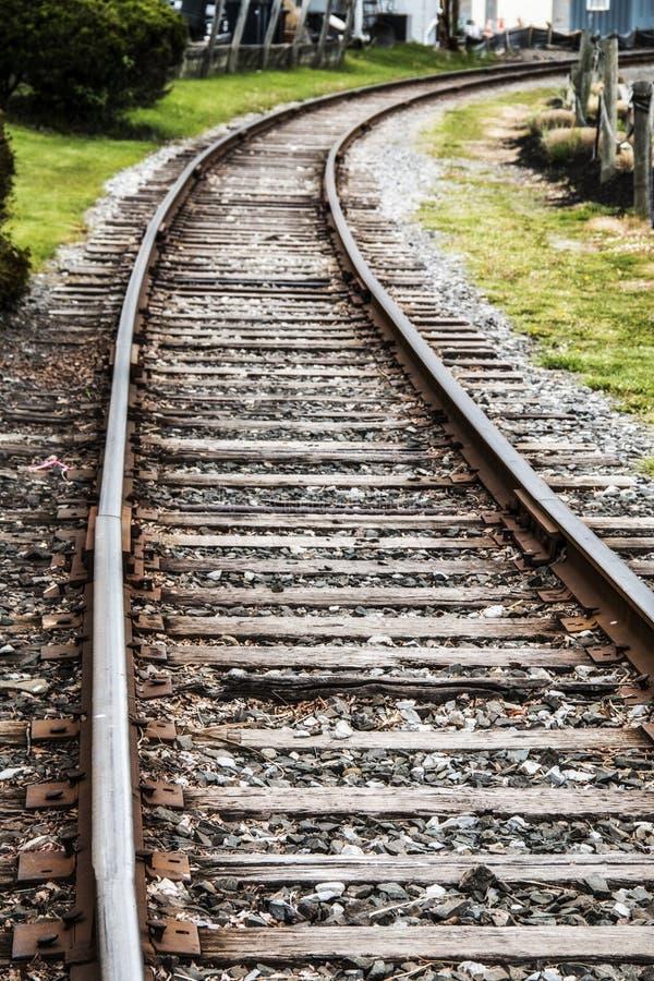 Voies ferrées de fer menant à une station de train photos libres de droits