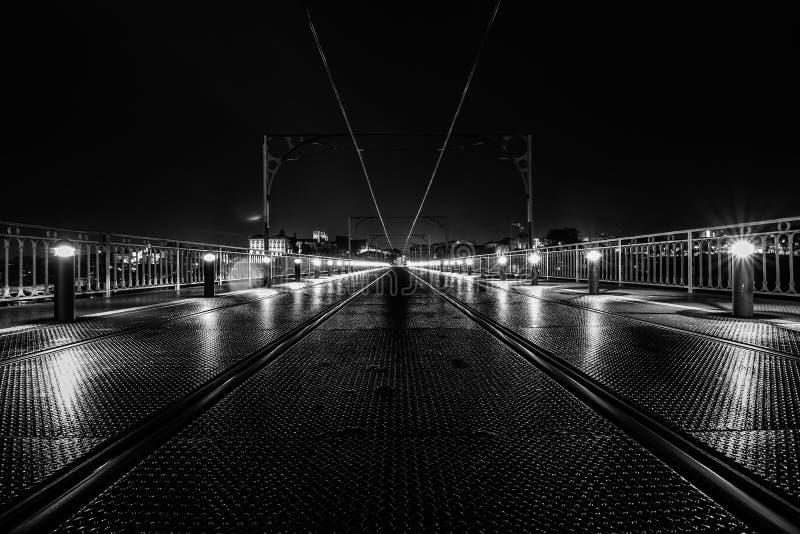 Voies symétriques de tram sur le pont de Dom Luis I la nuit à l'arrière-plan, Porto, Portugal Image noire et blanche photo stock