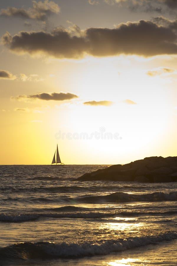 Voile de bateau dans l'horizon au coucher du soleil de mer image stock