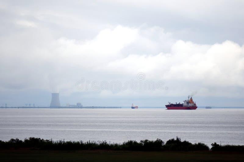 Voile de cargos de bateau-citerne et par la centrale nucléaire images stock