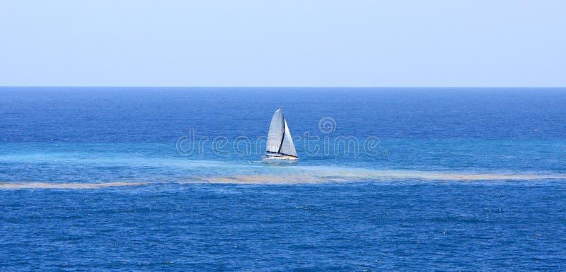 Voiles de catamaran par la pollution dans l'océan images libres de droits