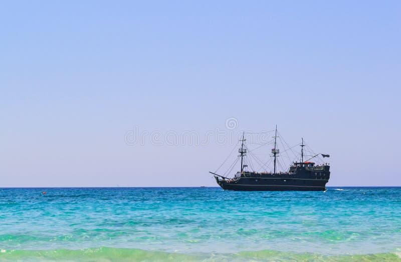 Voiles noires de bateau de pirate le long de la côte photo stock