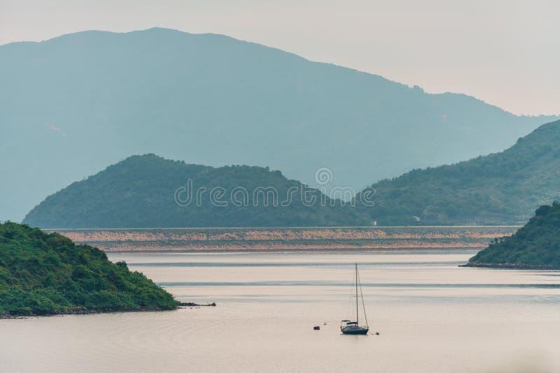 Voilier éloigné flottant sur l'eau de lac sur le fond vert de montagnes Vue scénique de crique de pluvier des villas de LAN de Sh photos stock