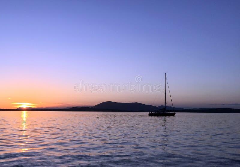 Voilier au coucher du soleil chez Sidney Spit, outre de la côte de l'île de Vancouver, AVANT JÉSUS CHRIST images stock