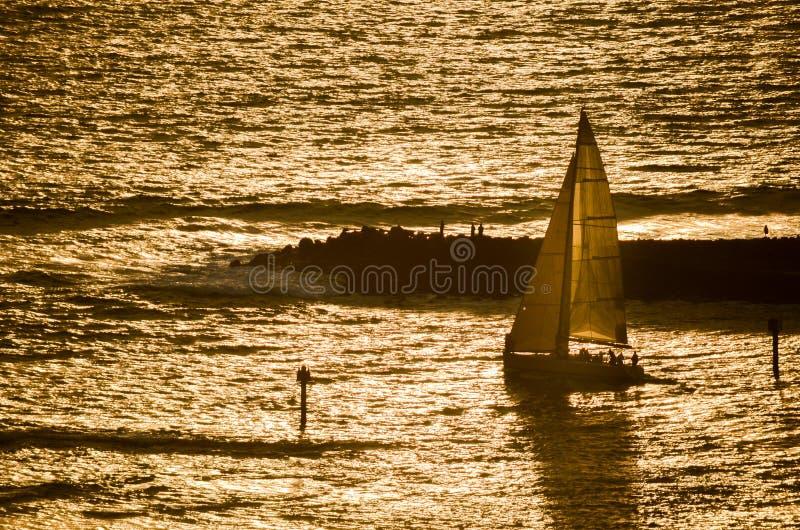 Voilier dirigé au coucher du soleil en Hawaï image libre de droits