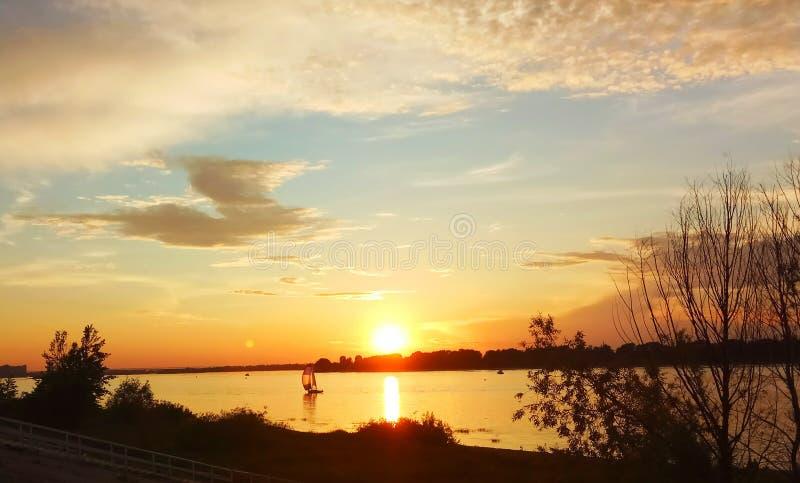 voilier isolé sur la rivière contre le coucher de soleil photographie stock libre de droits