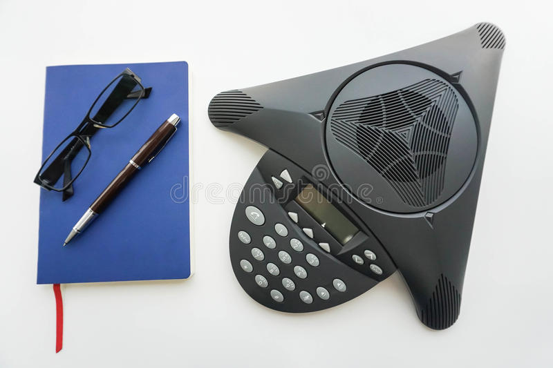 Voip IP conference phone with notebook and eyeglasses for taking minute of meeting in office stock photo