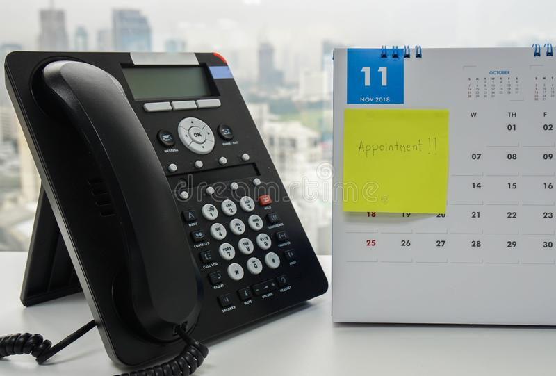 VOIP IP phone for conference call meeting in November calendar with sticky note of appointment reminder on office desk. Close up VOIP IP phone for conference stock photography